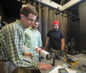 a professor works with students on the optics lab laser