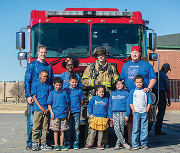students from TU and Kendall Whittier smile in front of a fire truck