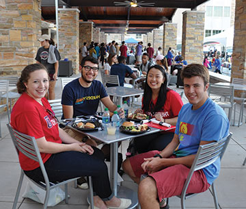 students smile looking up from their food at the Student Union patio